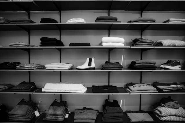 grayscale photography of assorted apparels on shelf-rack